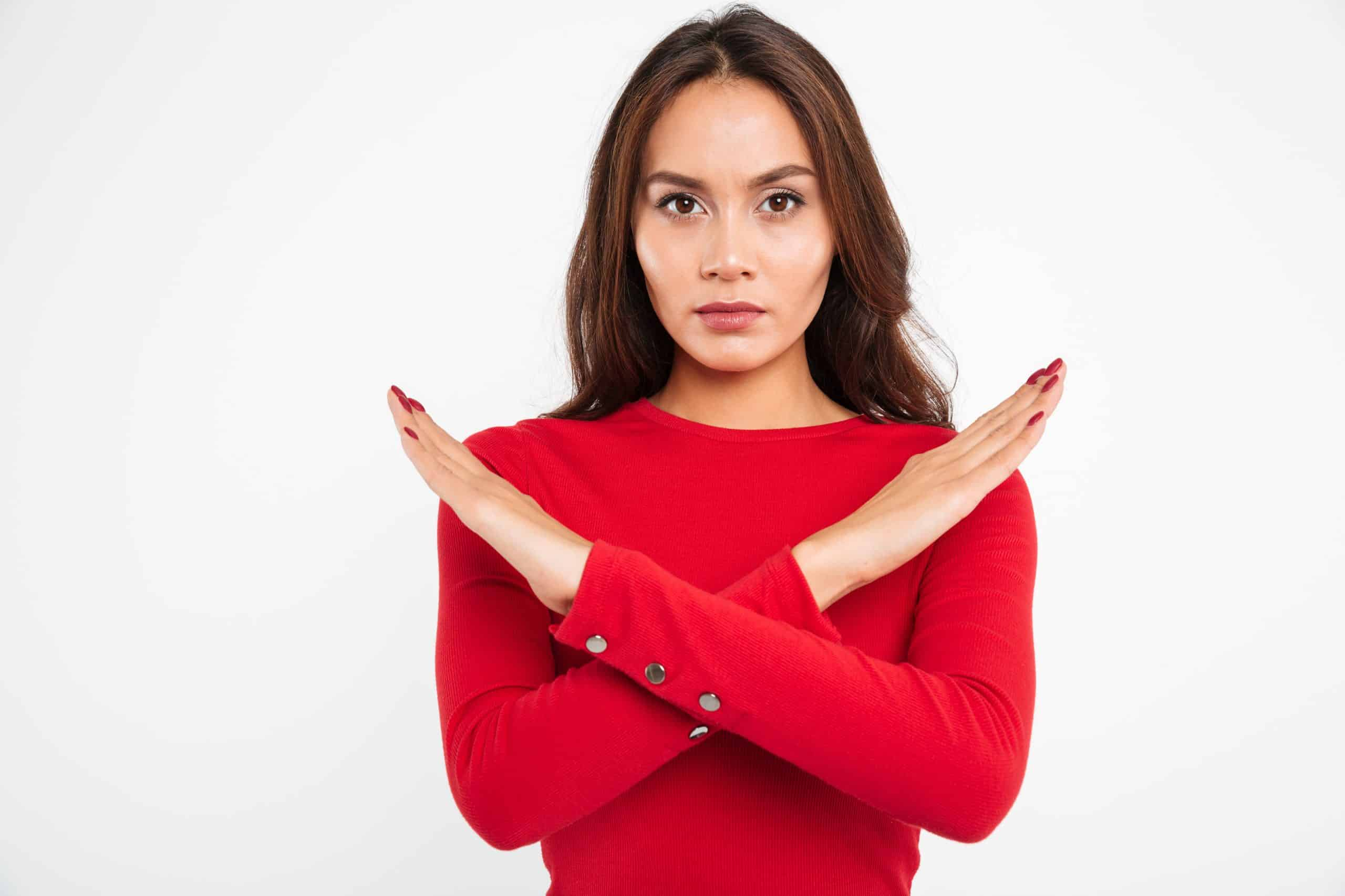 woman showing stop gesture with crossed hands
