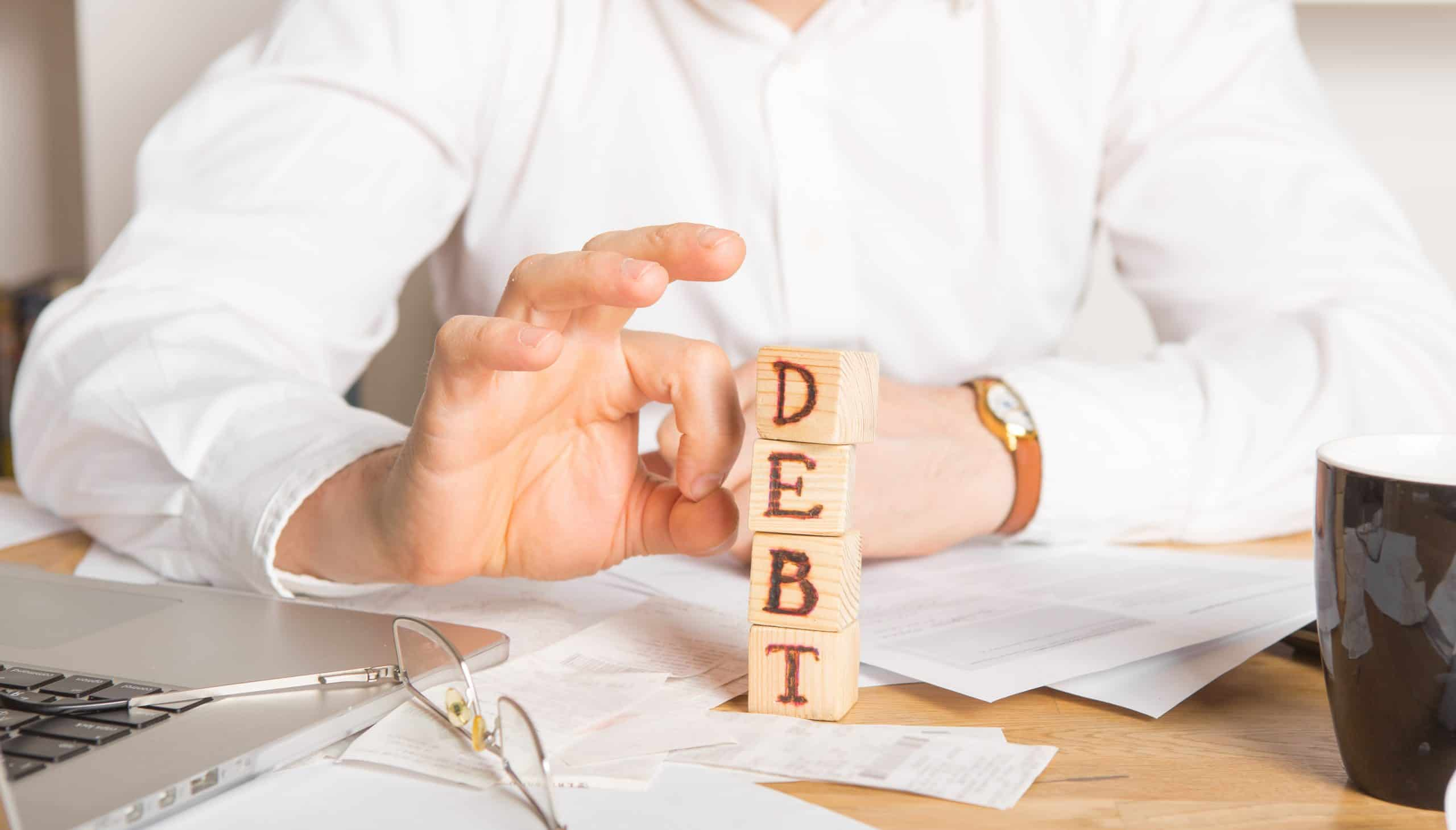 Businessman removes wooden blocks with the word debt