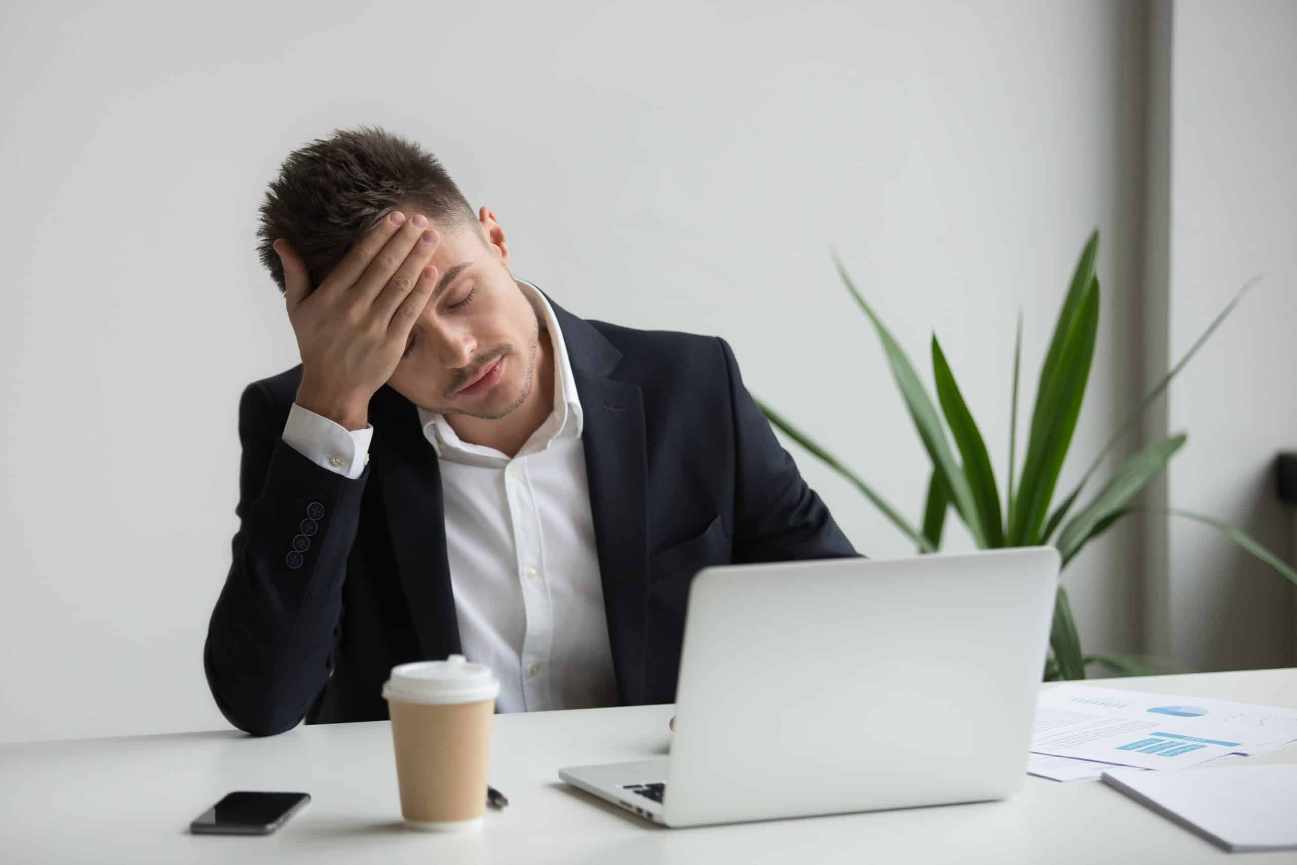 Frustrated businessman having strong headache