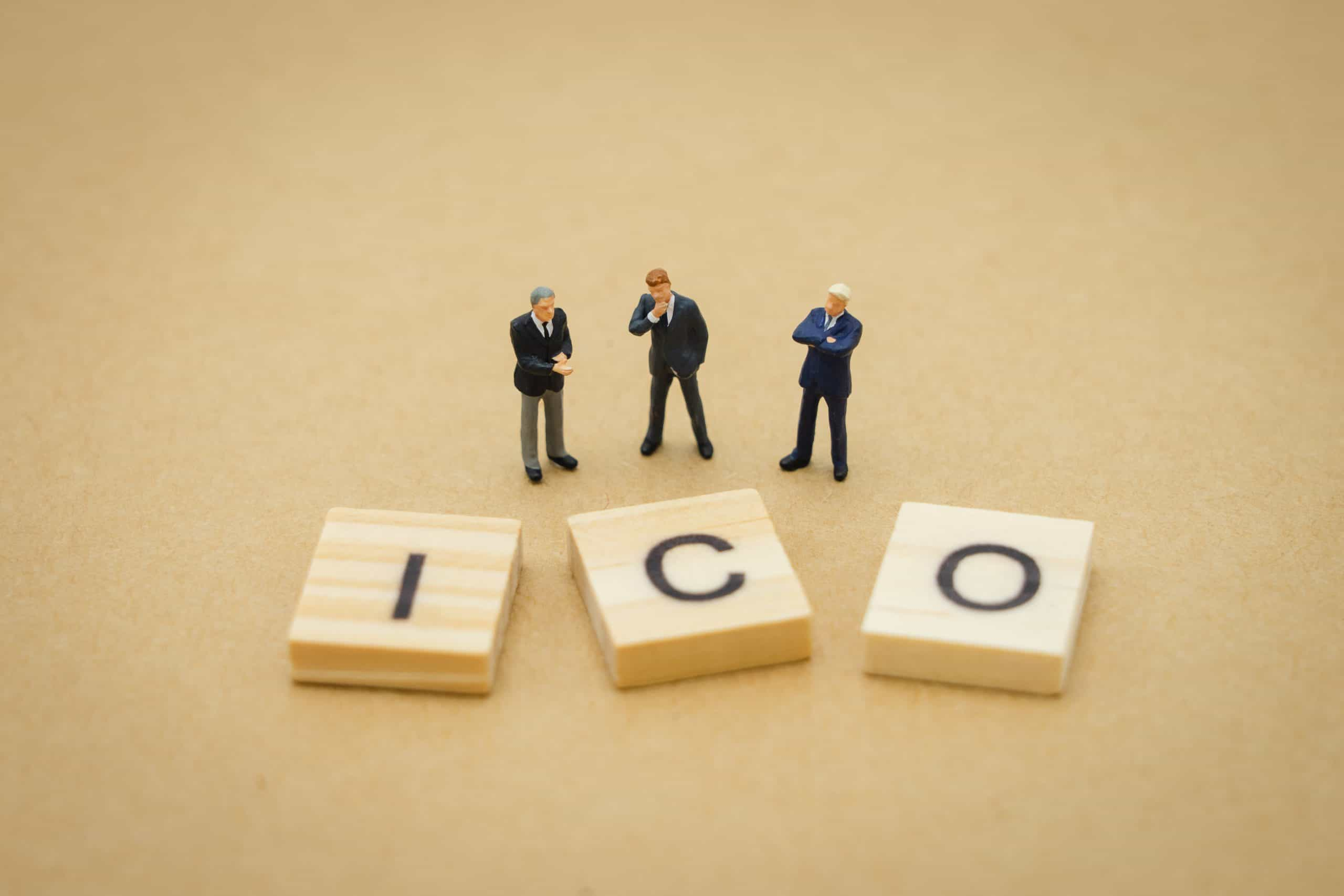Miniature people businessmen standing with wood word icon