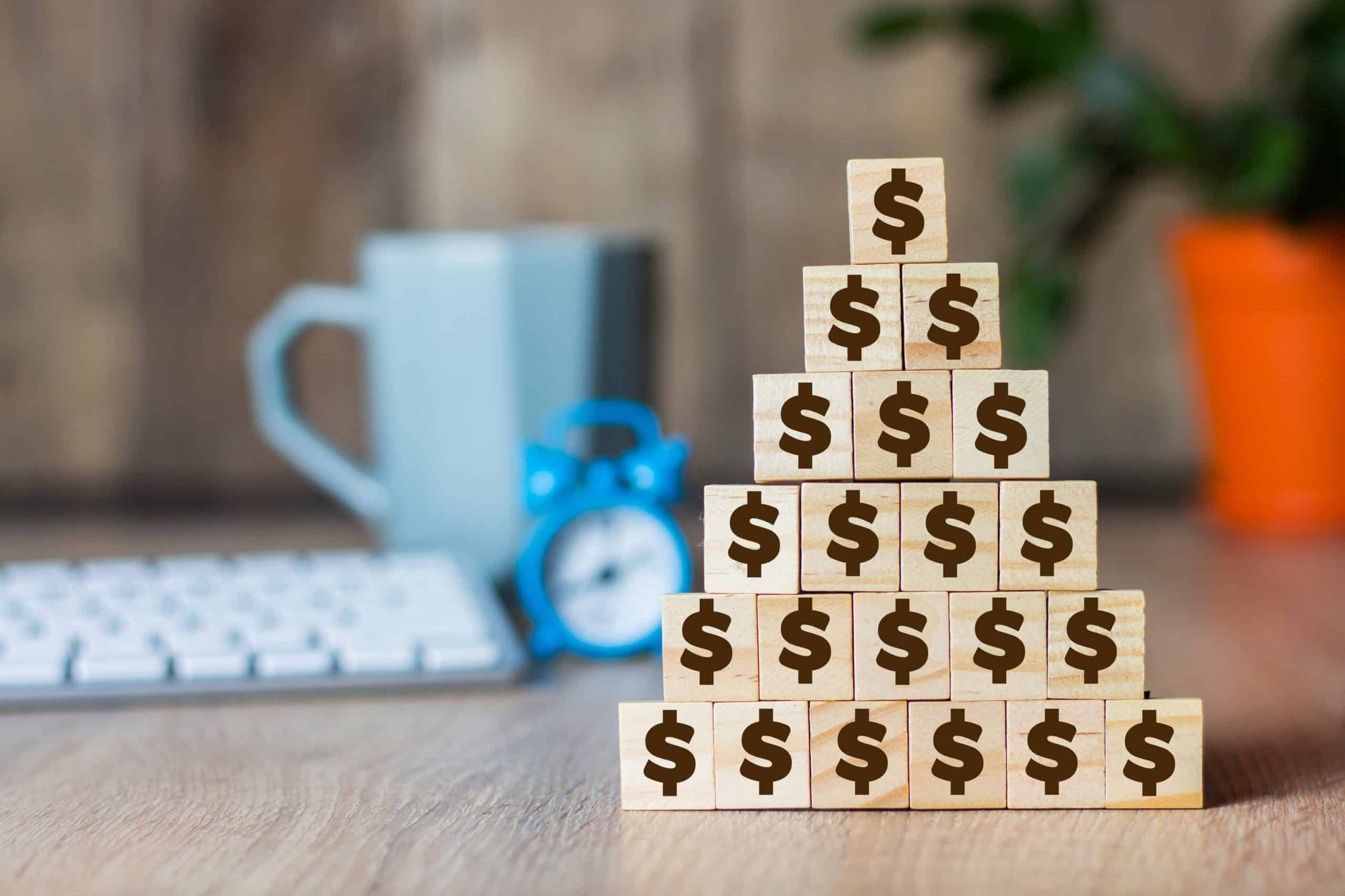 Wooden cubes with a dollar sign lined up with a pyramid